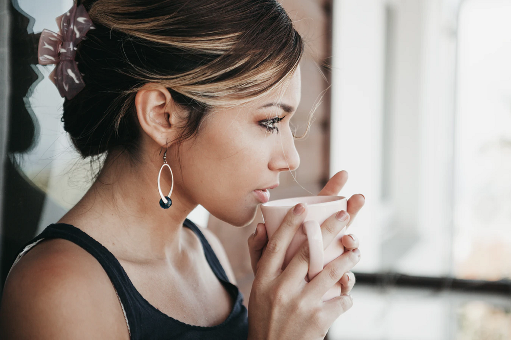 Side view of beautiful young woman drinking coffee